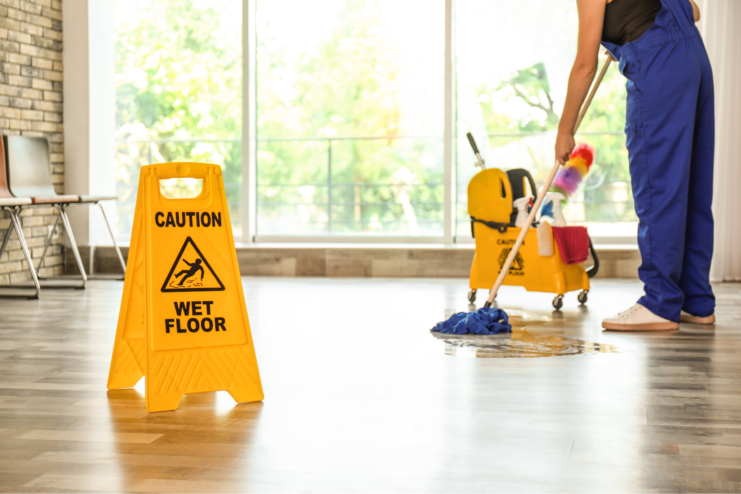 Person mopping floor with wet floor sign. Star Clean Ltd, Cleaning, Cleaners, Commercial Cleaners, Domestic Cleaners. Bath, Bristol
