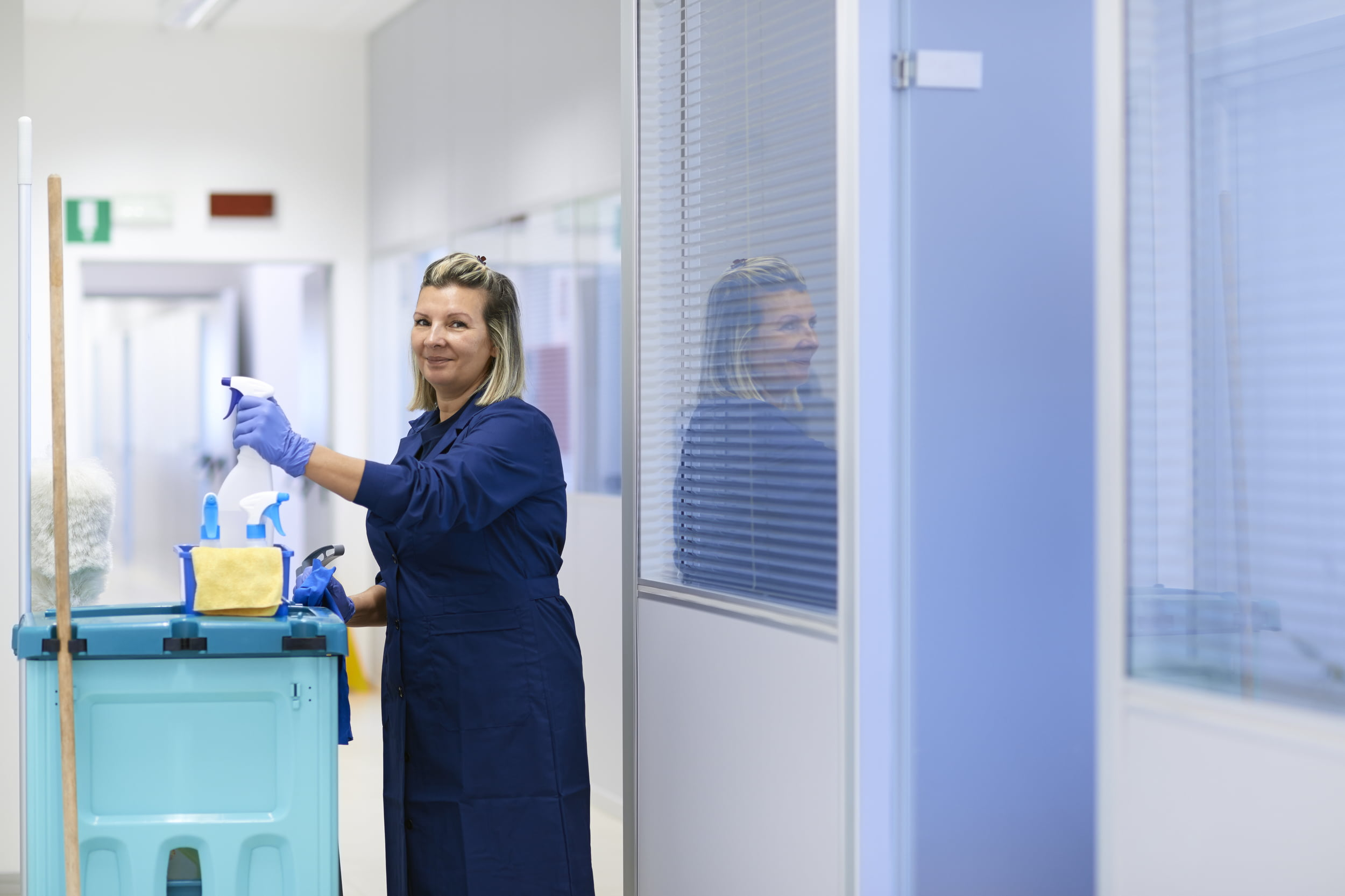 White woman in blue overalls in office environment with cleaning trolley. Star Clean Ltd, Cleaning, Cleaners, Commercial Cleaners, Domestic Cleaners. Bath, Bristol