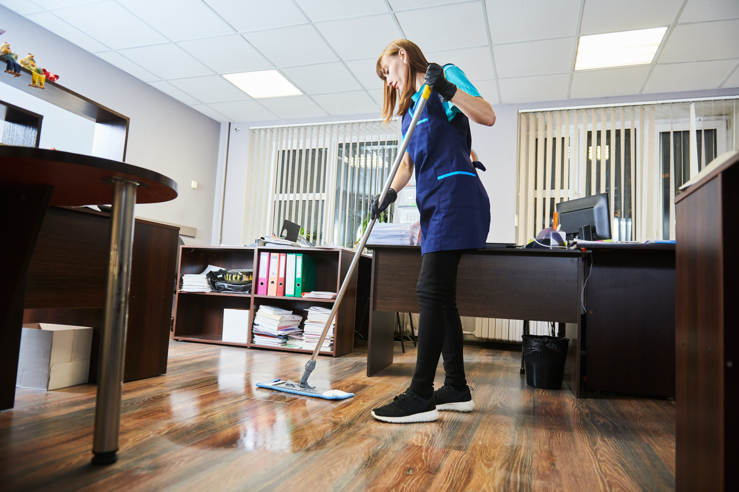 White woman in blue uniform mopping floor. Star Clean Ltd, Cleaning, Cleaners, Commercial Cleaners, Domestic Cleaners. Bath, Bristol