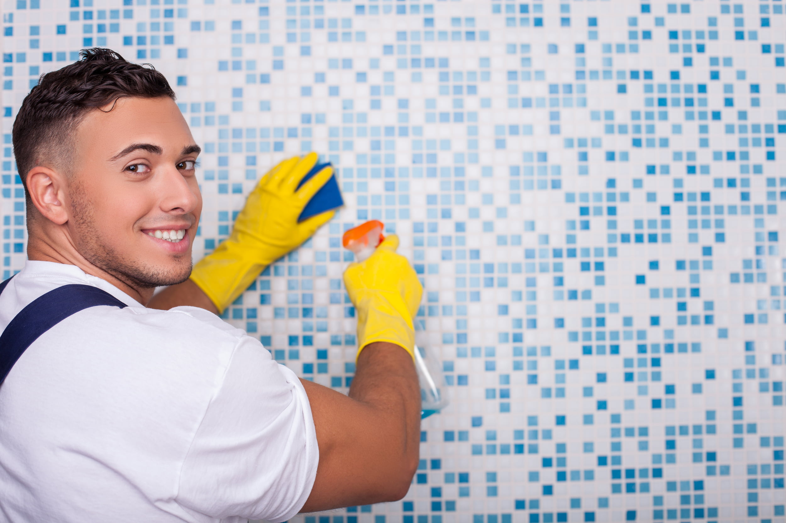 White man in white shirt an blue overalls, cleaning tiles. Star Clean Ltd, Cleaning, Cleaners, Commercial Cleaners, Domestic Cleaners. Bath, Bristol
