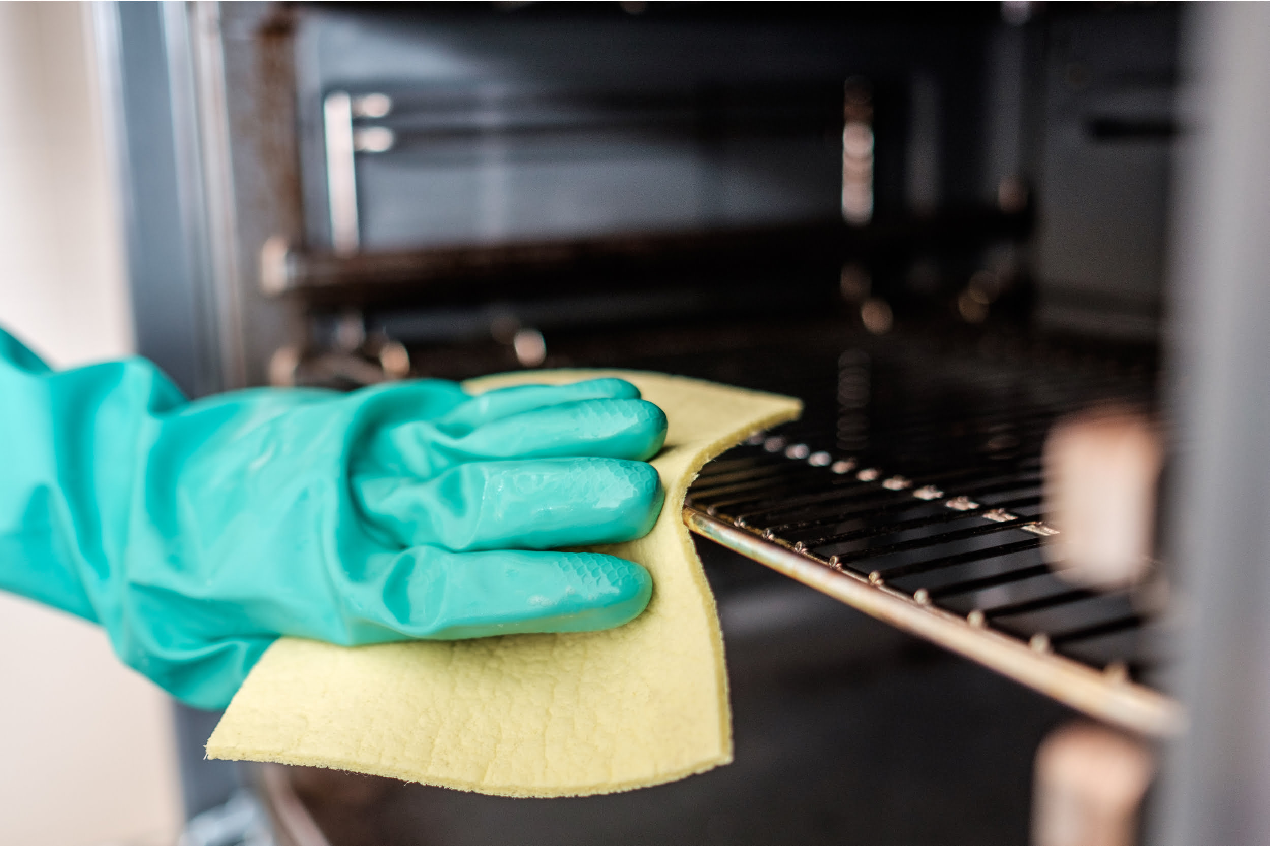 Green rubber gloved hand cleaning oven. Star Clean Ltd, Cleaning, Cleaners, Commercial Cleaners, Domestic Cleaners. Bath, Bristol